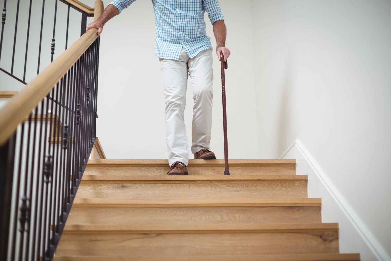 senior-man-climbing-downstairs-with-walking-stick