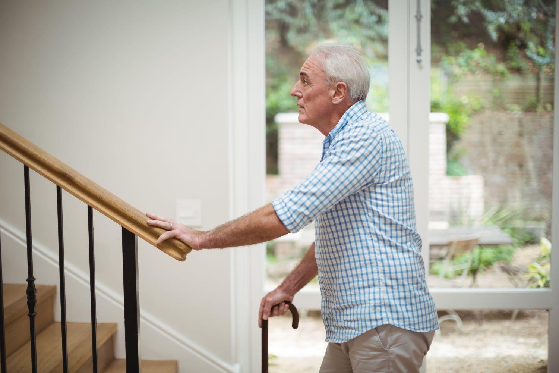 senior-man-climbing-upstairs-with-walking-stick